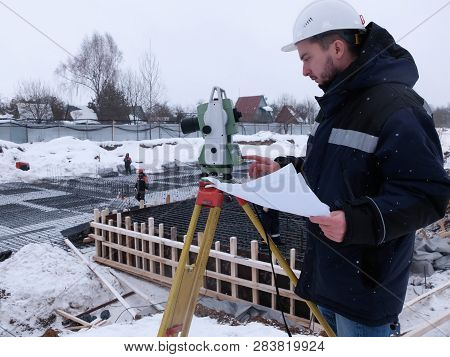 Bearded Geodetic Engineer-surveyor In White Hardhat Works On The Geodetic Total Station Holding A Dr