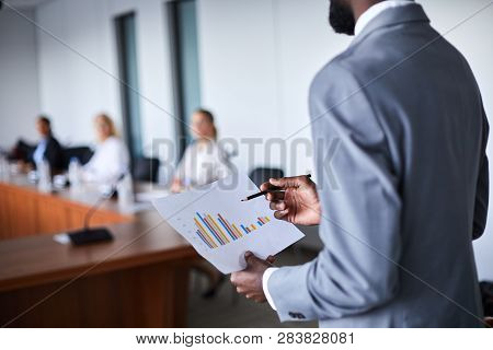 Young Elegant Economist Holding Paper With Financial Chart While Making Report For Colleagues At Con