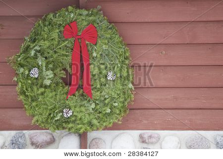 Wreath On Log And Stone Cabin Wall.