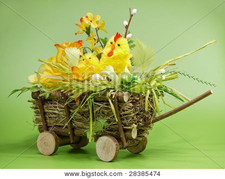 Wicker cart with Easter chick and eggs over light green background