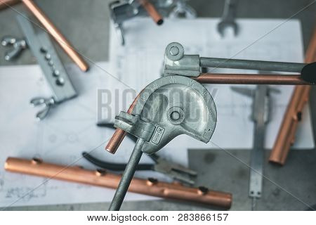 Pipe bender tool in a hands of factory worker on a factory workbench background. Fitter is bending a pipe. Pipework. poster