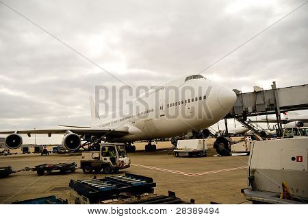 Air travel - A parked plane is loading off Passengers in an airport