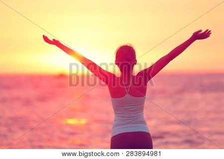 Wellness, well-being and happiness concept. Silhouette of woman with open arms raised to the sky on sunset beach practicing yoga.