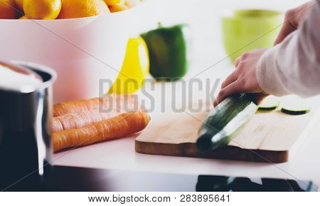 Cutting a cucumber on wooden board. Preparing meal of vegetables.
