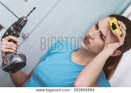 Young woman with cordless and measure repairing in home. DIY concept.