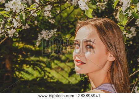 Blonde woman in garden with blooming trees. Green spring background.