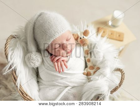 Little baby in hat covered in white blanket sleeping in basket with toy