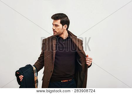 Always Perfect. Stylish Dark-haired Man Standing, Holding His Coat And Looking Away Isolated Over Wh