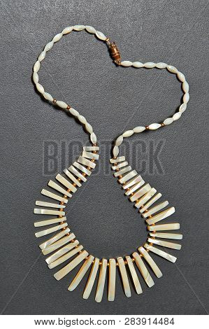 Beautifull Nacre Necklace On  Black Textured Wooden Table