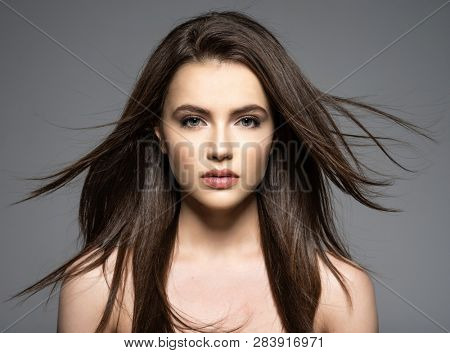 Brunette woman with beauty long brown hair. Fashion model with long straight hair. Fashion model posing at studio.