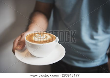Hand Holding Latte Or Cappuccino With Frothy Foam, Coffee Cup Top View In Cafe.