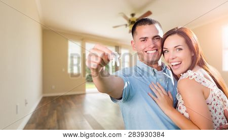 Young Military Couple with House Keys In Empty Room of New Home.