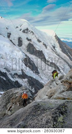Mountain Guide And A Male Client On A Rock And Snow Ridge Heading Towards A High Summit In The Frenc