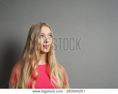 Contemplative Young Teenage Woman Looking Up - Gray Wall Background With Copy Space