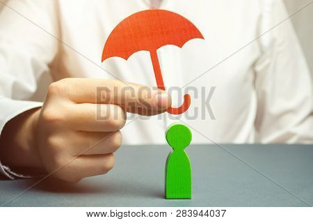 Insurance Agent Holding An Umbrella Over A Human Figure. Concept Of Life And Health Insurance. Secur