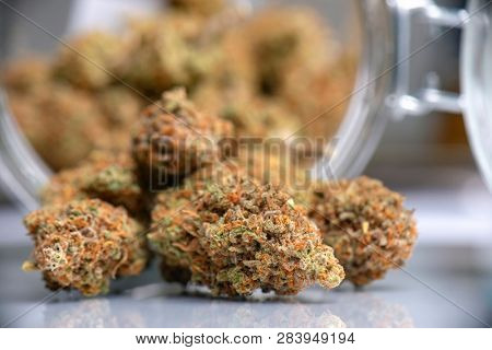 Detail of dried cannabis buds pouring from a jar, medical cannabis dispensary concept