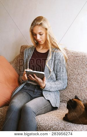 Teenage Girl Using Tablet Computer At Home While Relaxing On Sofa With Cat - Candid Real People Life