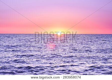 Purple Landscape With Sea And Sunset. Evening Sun Over Ocean. Beautiful Scenery With Sunrise Over Se
