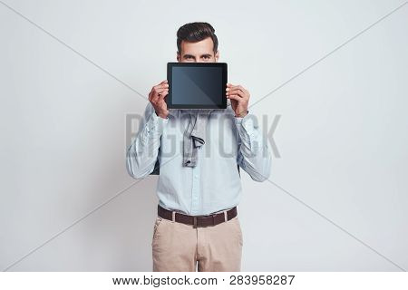Look Over Here. Attractive Young Man Holding Digital Tablet In Front Of His Face On A Grey Backgroun