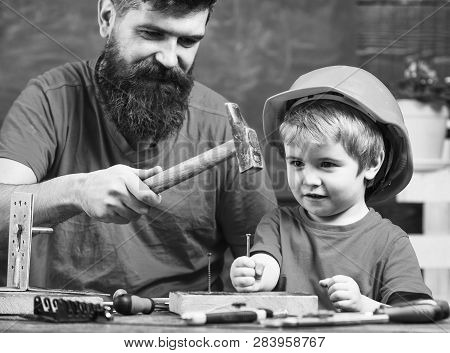 Boy, Child Busy In Protective Helmet Learning To Use Hammer With Dad. Father With Beard Teaching Lit