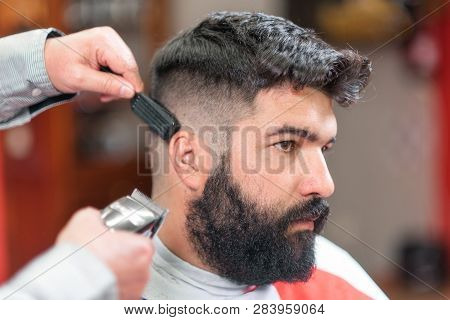 Handsome bearded man, getting haircut by barber, with electric trimmer at barbershop . poster