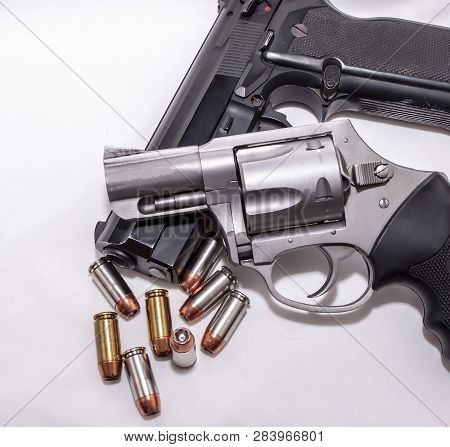 Two Handguns, A 40 Caliber Pistol And A 357 Magnum Revolver With 40 Caliber Bullets On A White Backg