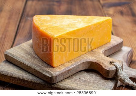 Piece Of Bright Yellow Hard Cheese Cheddar, Originating In The English Village Of Cheddar In Somerse