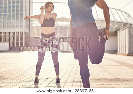 Warming Up Together. Close Up View Of Sporty And Healthy Couple Standing Outside And And Warming Up