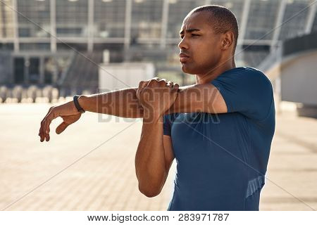 Preparing For Workout. Close Up Portrait Of African Athlete Stretching His Arms During Morning Worko