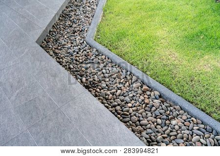 Black And Brown Stone Decorated In Between Walkway And Lawn. Landscape Design Detail.