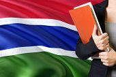 Learning Gambian language concept. Young woman standing with the Gambia flag in the background. Teacher holding books, orange blank book cover. poster