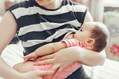 Woman breast feeding baby. Baby feeds on mother's breasts milk. Newborn baby is breast feeding closeup. Breastfeeding baby poster