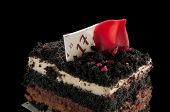 Tiered chocolate cake with a crumbled topping isolated on a black background poster