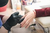 The manicurist in black latex gloves covers the nails with a colored gel polish in the beauty salon. poster
