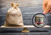 Money bag with the word Startup and dollars on the scales. Analysis of funds raised and verification of the goals of a startup. Return of money to investors after a failed startup. Achieving the fundraising goal poster