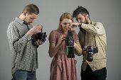 Focus on what matters. Paparazzi or photojournalists with vintage old cameras. Group of photographers with retro cameras. Retro style woman and men hold analog photo cameras. Photography studio. poster