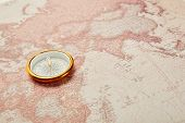 The golden compass on vintage world map poster