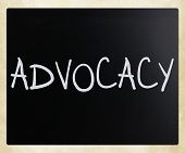 The word 'Advocacy' handwritten with white chalk on a blackboard poster