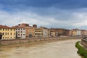 Old colorful buildings along the Arno river. Pisa cityscape. Embankment of the Arno river in Pisa. Gloomy rainy and cloudy day. Pisa, Italy. poster