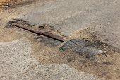 Very bad quality road with potholes. Hole in asphalt, bad asphalt. Pit, unsafe, hole road. Transportation, destruction of roads, risk of movement by car concept. Bad roads concept poster
