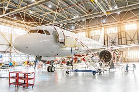 Aviation Hangar With Passenger Aircraft Jet For Maintenance.