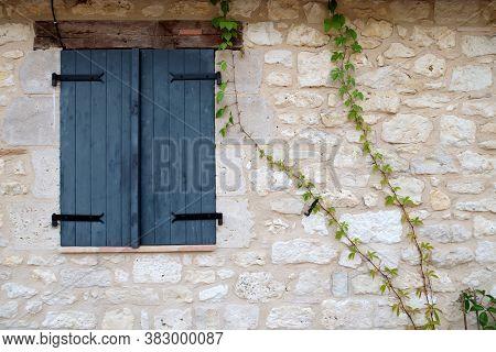 Dark Grey Window Shutters Closed In A Stone Wall Surround