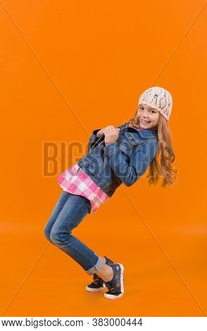Girl Model With Long Blond Hair Smile And Balance Tiptoe. Child In Jeans Suit, Hat, Plaid Shirt On O