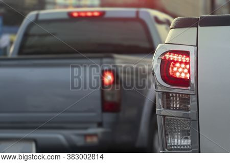 Close Up Rear Light Of Pick Up Car. Turn On The Brake Lights And Have Another Car.
