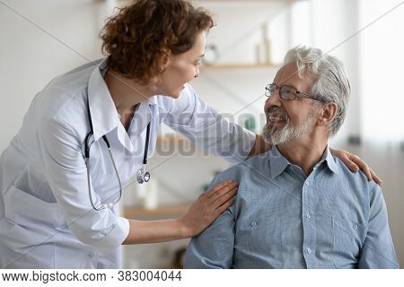 Smiling Young Nurse Caregiver Supporting Mature Patient During Homecare Visit