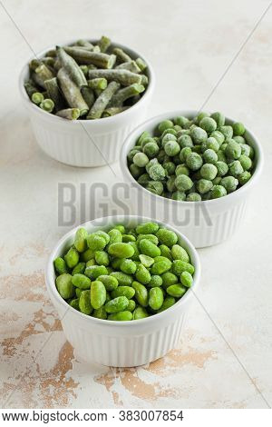 Frozen Vegetables Such As Green Peas, Soy, Green Beans And Baby In White Bowls. Healthy Food, Frozen