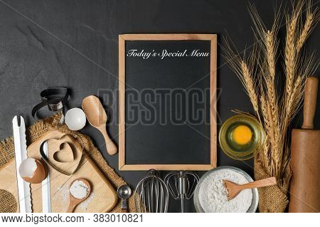 Menu Text On Blackboard And Fresh Eggs, Cake Flour  With Kitchen Utensils For Pastries On Black Tabl