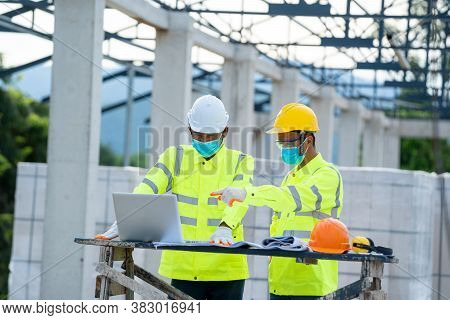 Construction Manager And Engineer Wearing Protective Mask To Protect Against Covid-19 Use Laptop Wor