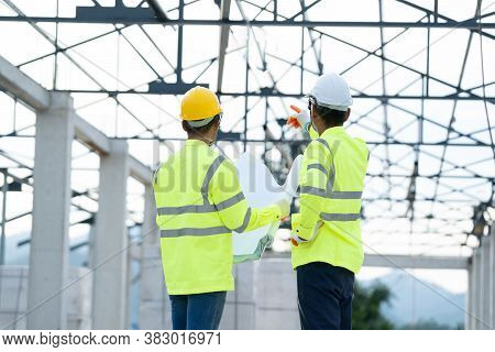 Construction Manager And Architect Working On Building Site.