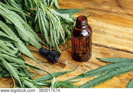 Cannabis Oil (cannabidiol Cbd).  Medical Cannabis (marijuana) And Extract On Wooden Background.